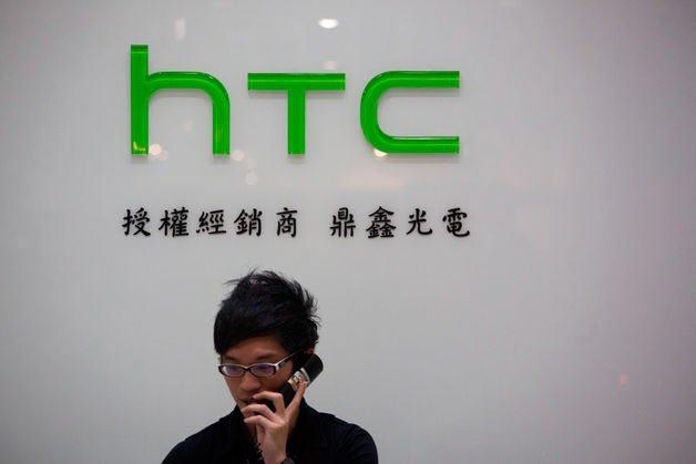 Мужчина разговаривает по телефону на фоне логотипа HTC